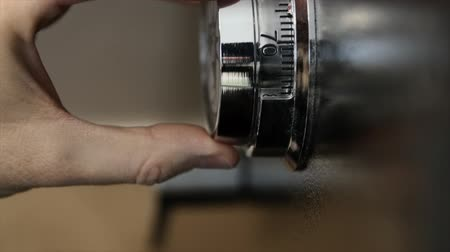 тайна : A man turns the dial on a safe to unlock it