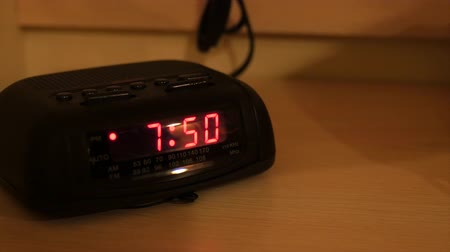 clock hands : An alarm clock in a hotel bedroom panning shot