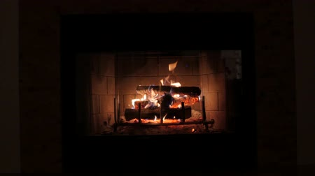 égés : A jib shot of a wood burning fireplace at night in the living room of a house