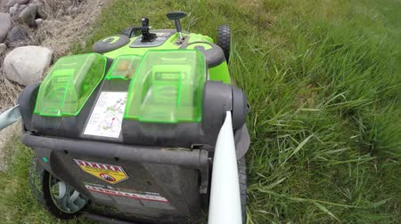 motor : A man mows the tall grass in the lawn with an electric lawn mower before a storm comes