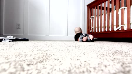 ползком : a baby plays by his crib Стоковые видеозаписи