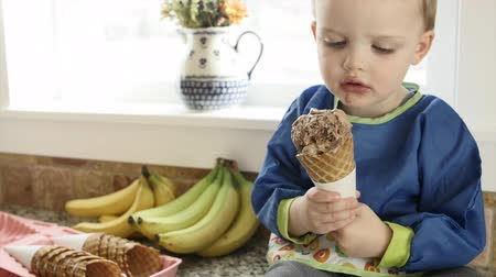 besinler : A mother scoops chocolate and vanilla ice cream into a waffle cone for her toddler boy in the kitchen.
