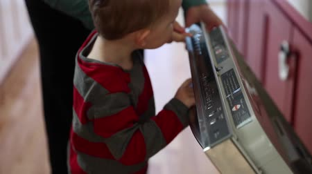 bulaşıklar : a little boy helps his mother start the dishwasher in the kitchen