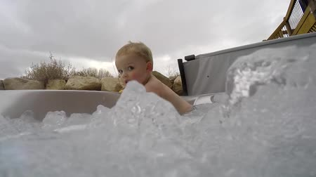 küvet : a little toddler boy in hot tub spa with bubbles in extreme slow motion shot 120fps
