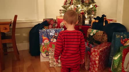 csomagolópapír : a little boy looking at his christmas presents under the tree Stock mozgókép