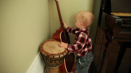 kytara : a toddler boy playing with a guitar