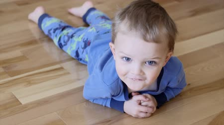 hazugság : A little boy lying on a wood floor in his home staring at the camera