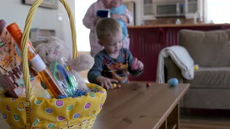 koszyk wielkanocny : A little boy on easter morning searching for his easter basket and eggs with his family in his home Wideo