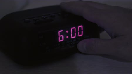 clock hands : A man hits snooze when his alarm goes off at six in the morning