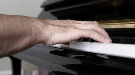 enstrüman : A man plays arpeggios on the black piano in his house