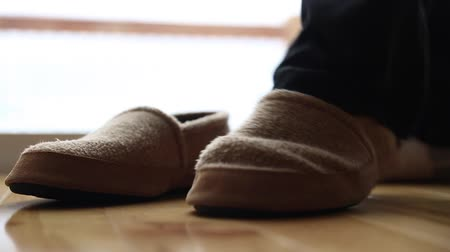 konfor : a man puts on a pair of comfortable slippers inside his home Stok Video