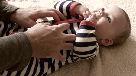 otcovství : A father plays with his baby on a blanket on a blanket in the living room