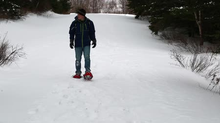 buty : a man hiking in snowshoes toward the ocean coastline Wideo