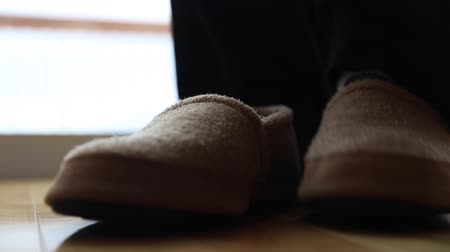 comfortable : a man puts on a pair of comfortable slippers inside his home Stock Footage
