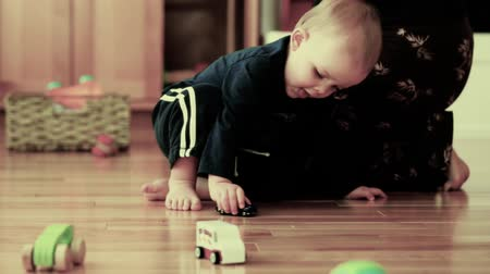 pisos : a mother and boy playing with toy cars