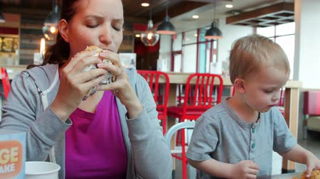 sanduíche : A young mother with her toddler son eating a lunch at a clean and modern fast food restaurant Stock Footage