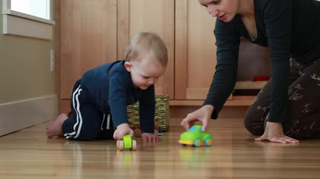 kalmak : a mother plays toy cars with her toddler boy