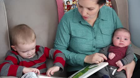 učit se : a mother reads a book with her toddler boy and newborn baby