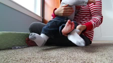 mudança : a mother putting on her little babies socks Stock Footage