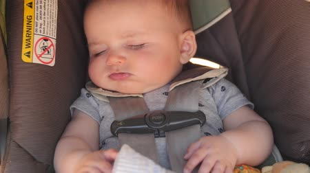 carseat : An adorable newborn baby boy sleeping in his car seat while traveling