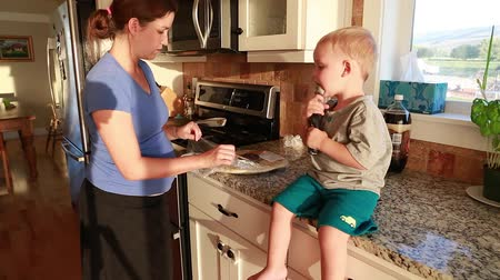 a pregnant mother and her toddler cooking pizza