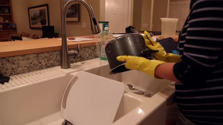 sıkıcı iş : a pregnant woman washing dirty dishes in her kitchen sink inside her home. dolly shot