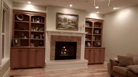 lareira : a jib shot of a cozy fireplace and mantle in a beautiful sitting room Vídeos