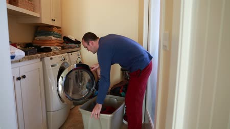 sıkıcı iş : a toddler helps his dad put clothes in the washing machine
