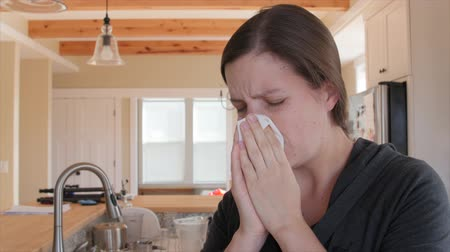 alergia : A sick woman grabs a tissue to blow her nose because she is sick with a cold Vídeos
