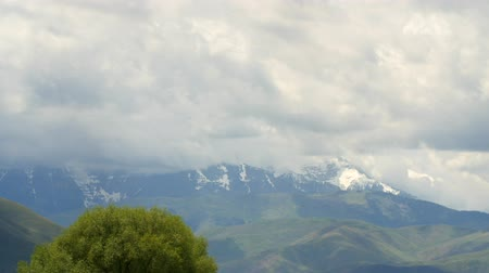 venkovský : A timelapse of storm clouds rolling over a large mountain range and valley fields