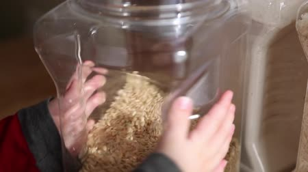 spiżarnia : a woman filling food containers with grains, flour, sugar, and other food.