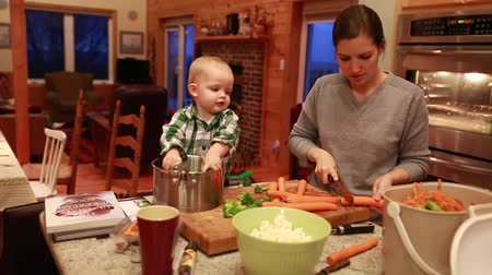 bıçak : a toddler helps his mother cook dinner while  in the kitchen