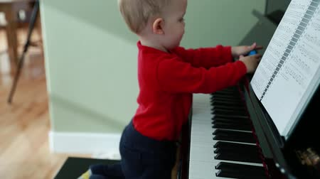 şarkı : a little toddler playing on a black upright piano in his home