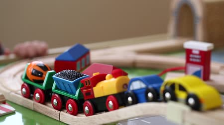 motor vehicle : a little boy plays with a toy train and cars as it runs along the track