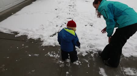 womanhood : a mother and her baby boy playing in the snow Stock Footage