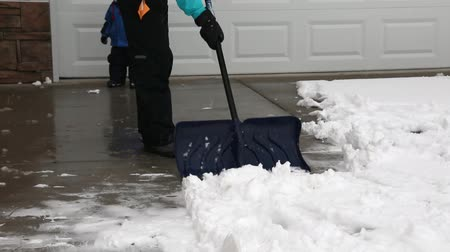 deep snow : a woman shovels snow off her driveway with her toddler after a snow storm Stock Footage