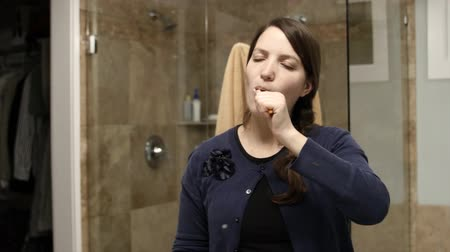 зубы : A woman brushes her teeth and gets ready for bed in her home bathroom Стоковые видеозаписи