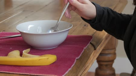 descamação : A woman eats a healthy breakfast of granola and yogurt with a banana