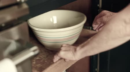 konyhai : a woman grabs a porcelain mixing bowl from her kitchen cabinets