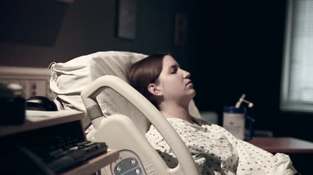 contraction : woman in labor having contractions at the hospital with nurses in the room Stock Footage
