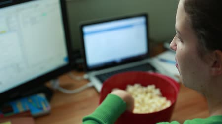 a woman snacking on popcorn in a home office