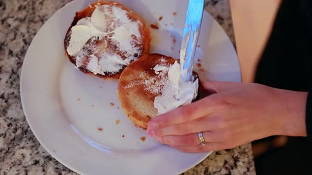 sýr : a woman spreading cream cheese on a bagel