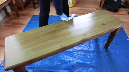 skvrny : a couple puts the final stain on a wood bench they painted