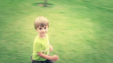 executar : a young boy running on grass