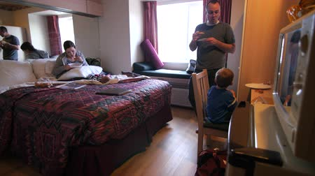 frigorífico : A young family eats pizza in a small hotel room