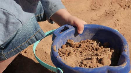 klapki : Adorable little boy filling bucket with sand on beach Wideo