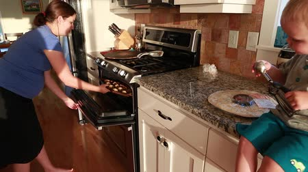konyhai : a pregnant woman and her toddler boy baking cookies and pizza in the kitchen for dinner