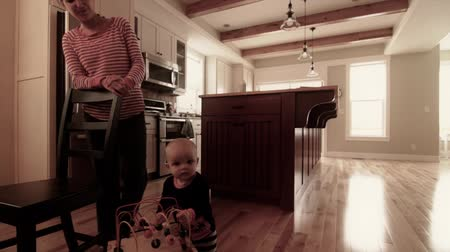 frigorífico : baby boy standing with toy in kitchen Stock Footage
