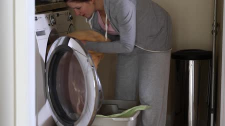 máquina : a mother puts the dirty laundry into the washing machine