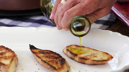 descamação : a woman pours olive oil on baguettes for fresh italian bruschetta